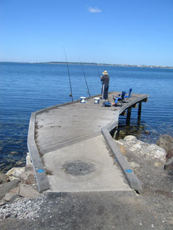 A man fishing at the fishing platform.