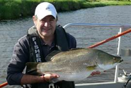 Fisherman Holding a Barramundi