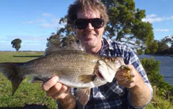 A young fisherman holding up a large estuary perch
